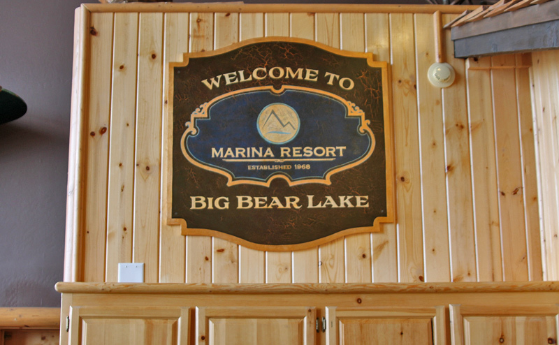 This sign was made on MDO sign plywood with a multiple layered crackle finish background, then hand painted and gold leafed followed by our antiquing process. We recently installed this in the lobby of the Marina Resort in Big Bear Lake, California.