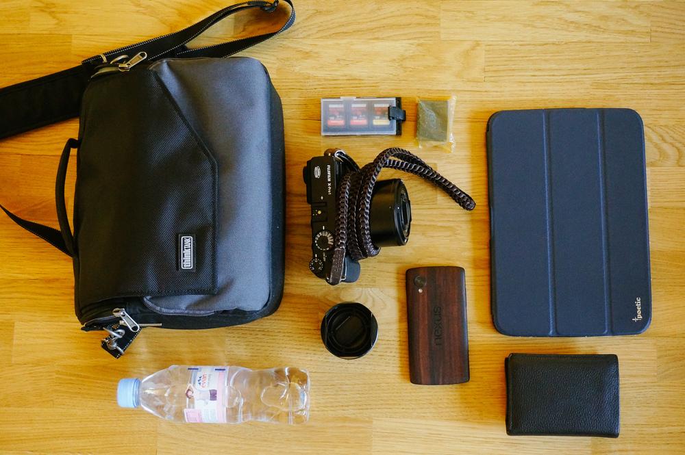 Dans mon sac: Fuji X-Pro 1 et son optique 60mm, objectif 35mm, batterie et cartes mémoire, tablette Nexus 10, téléphone Nexus 5, porte-monnaie et bouteille d'eau.