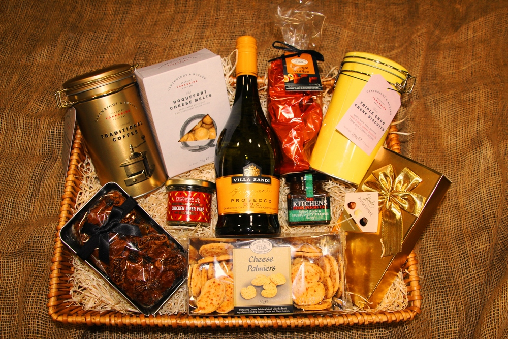 The Barlaston Hamper includes: - 75cl  Prosecco DOC, exceptional coffee blend in a reusable tin, triple chocolate biscuits in a reuseable tin, assorted Belgian chocolates, cheese palmiers, apricot & fig fruit cake, Patchwork artisan pate,  local chutney, Roquefort cheese melts, chocolate & orange truffles, gift basket, wood wool, gift wrapping, ribbon & bow