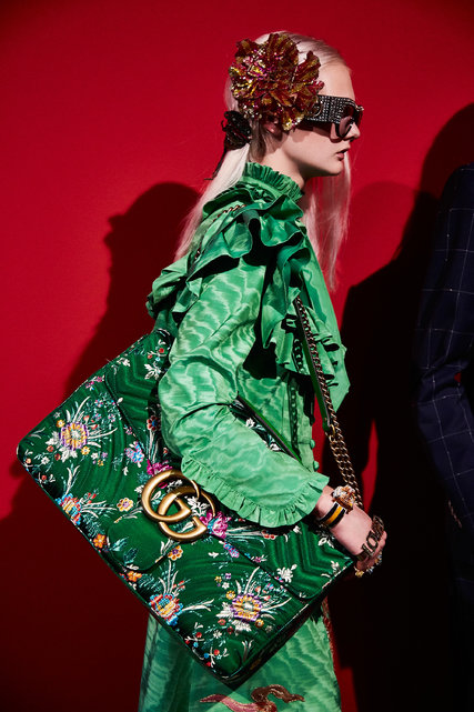 Did we already say exaggerated? We can always count on Gucci to show us how to fashionably break out of our shell. Gucci featured this over the top handbag fastened by a muted metal chain and emerald leather strap to match the gorgeous green background of this masterpiece of a bag!