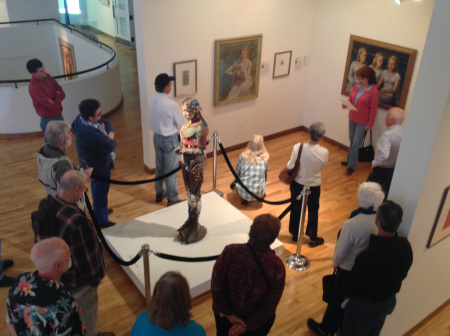 "For an ""Art of Poetry"" presentation, a contributor reads in front of The Three Sisters when it was part of the Faces and Figures from the HMA Collection exhibit in early 2014. In the foreground is Jef Raasch's Manimal."
