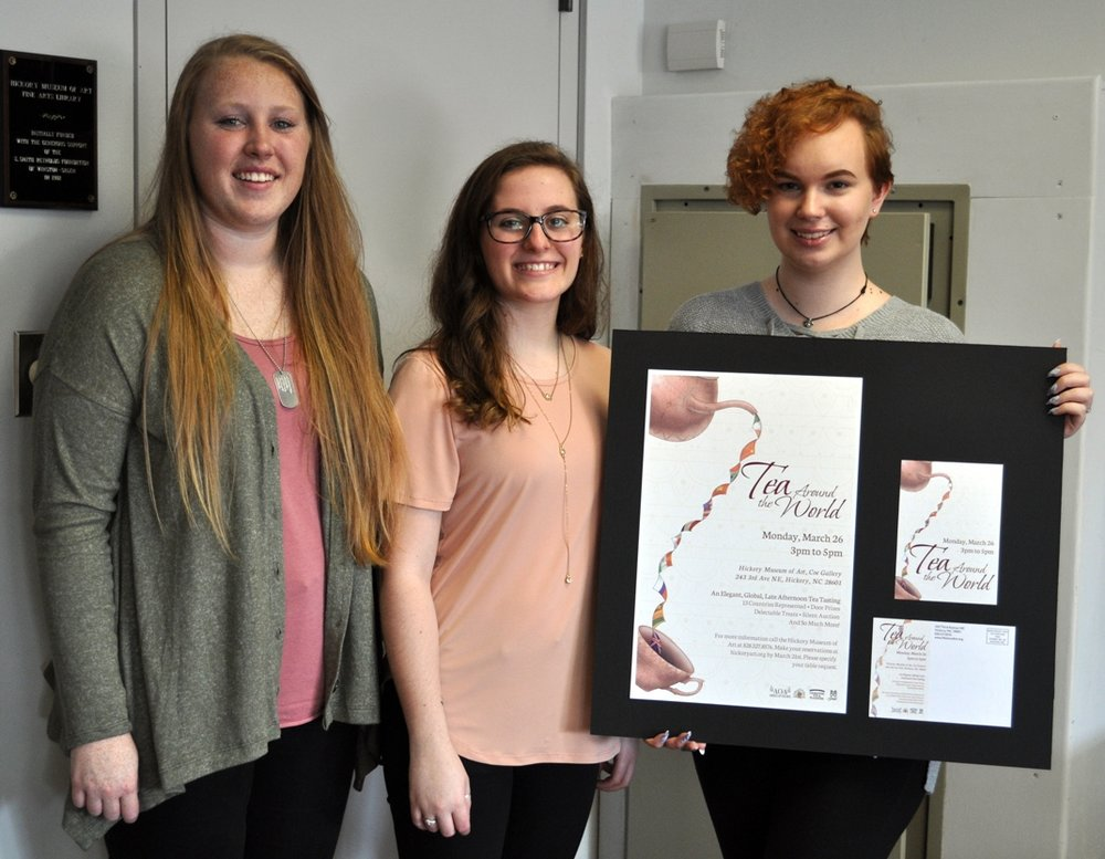 Kirsten Pierce (L); Carlee Wiswall (C); and DeLeslyn Brunfield (R), members of the Catawba Valley Community College student design team, display their advertising design chosen by the HMA Guild to promote Tea Around the World.