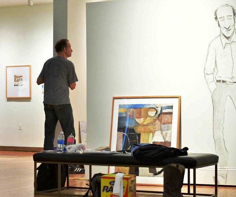 Diffee working with HMA staff on setting up for his HMA show, including drawing himself on the gallery walls. (Photo  Jason Overb .)