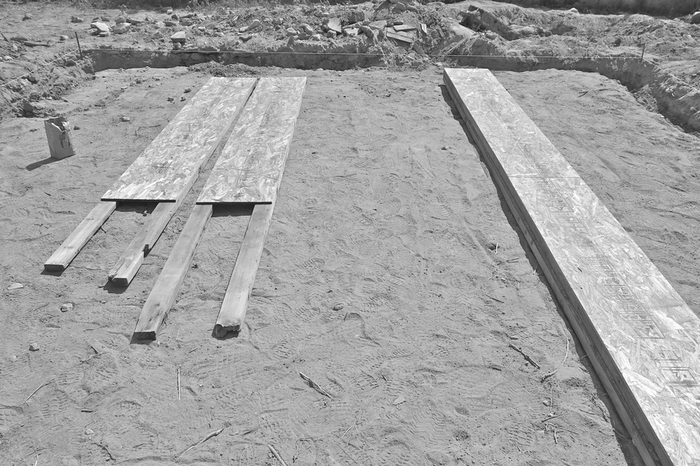 10 August 2014: Forms made from oriented strand board and 2x4s salvaged from the adobe bulwark we tore down . . . still a couple weeks from pouring the concrete.