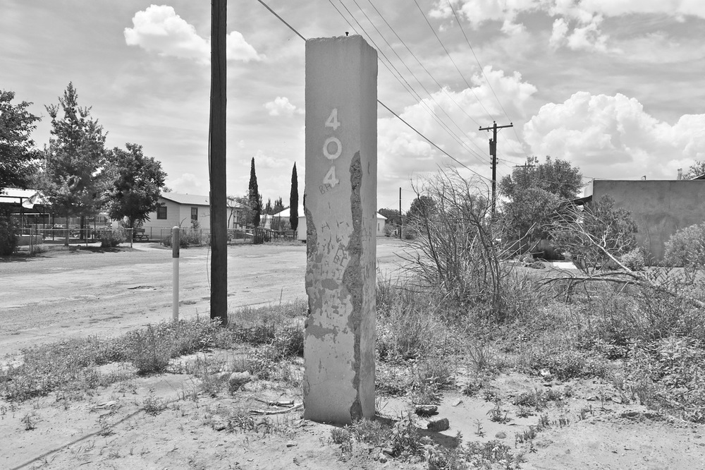 15 August 2014: We have a street address! This existing column, made from flesh-colored concrete, is covered with various carvings and graffiti. There used to be another one, on the other side, but it was gone before we got here. Last week, a woman drove by looking for the other one. When they were little, she said, her husband carved their names in a heart there.