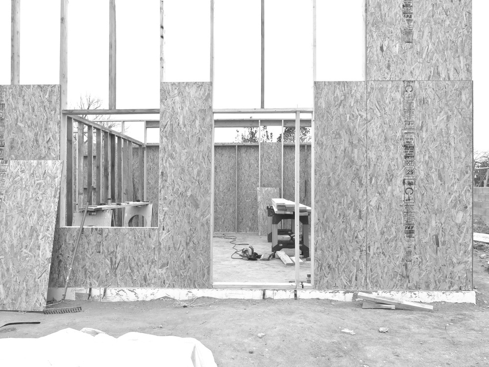 31 December 2014: Here is a section of the south wall. The square cutout on the left will be our picture window (double-paned single hung) and the human-sized rectangle on the right will be our front door.