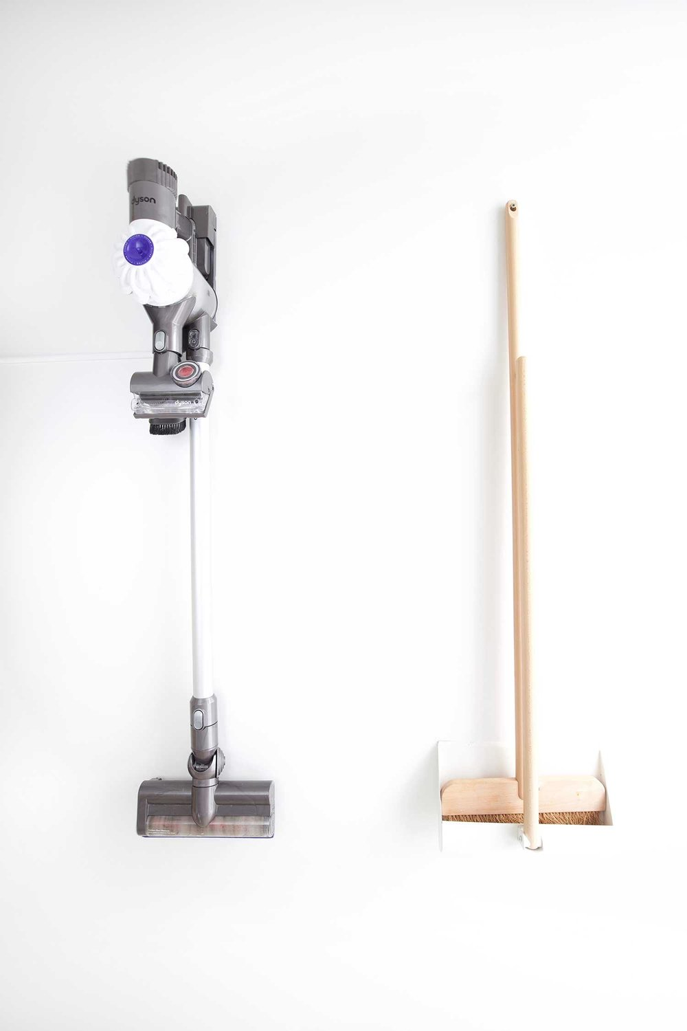 hanging vacuum and broom in organized pantry