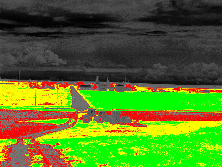 The NIR-VIS index returns a very reproducible vegetation map. Here we've applied a false coloring that scales from green (dense vegetation) to yellow to red to grey (no vegetation). Notice the tractors, houses, and roads have a low signal, while the fields have a higher signal.