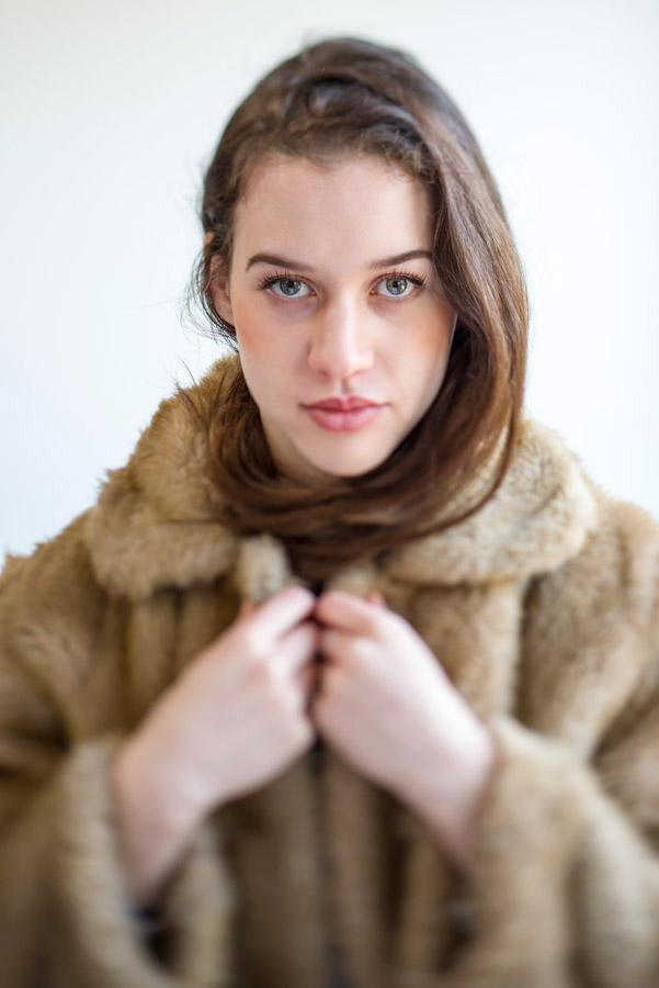 Portrait of a young woman wearing a fake fur coat.