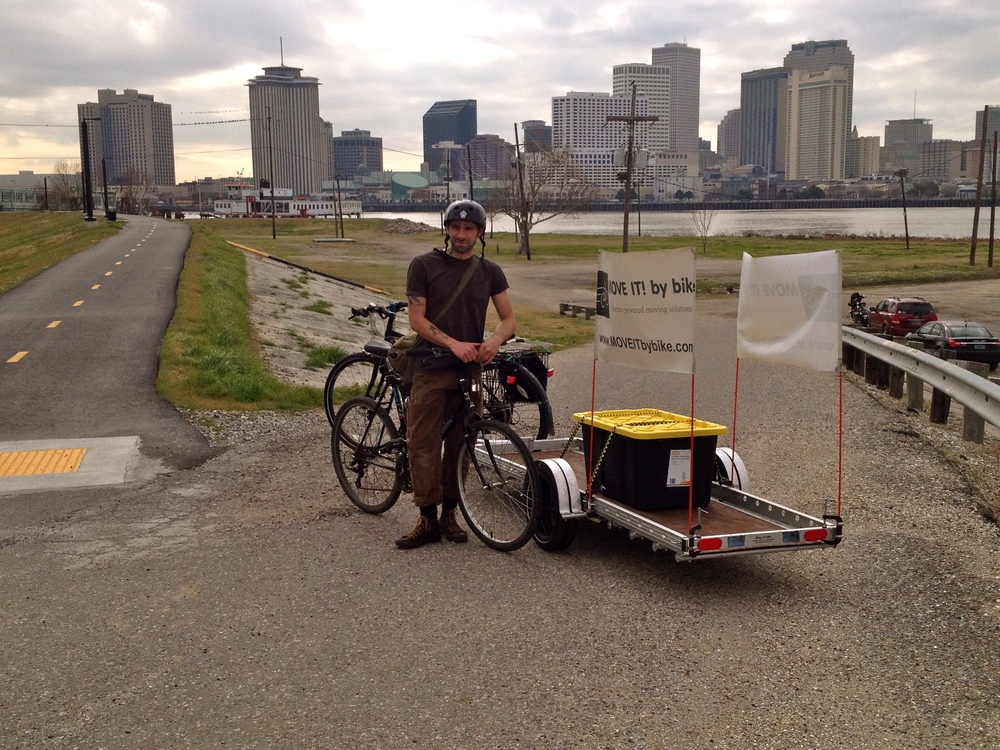 Paul and trailer on the bike trail on the levee in Algiers.  The ferry terminal and the CBD in the background.