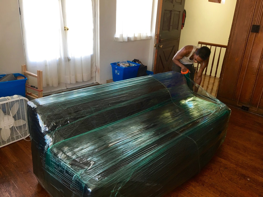 Wrapped in furniture blankets then wrapped in stretch wrap the couch is ready for its journey down four flights of winding stairs