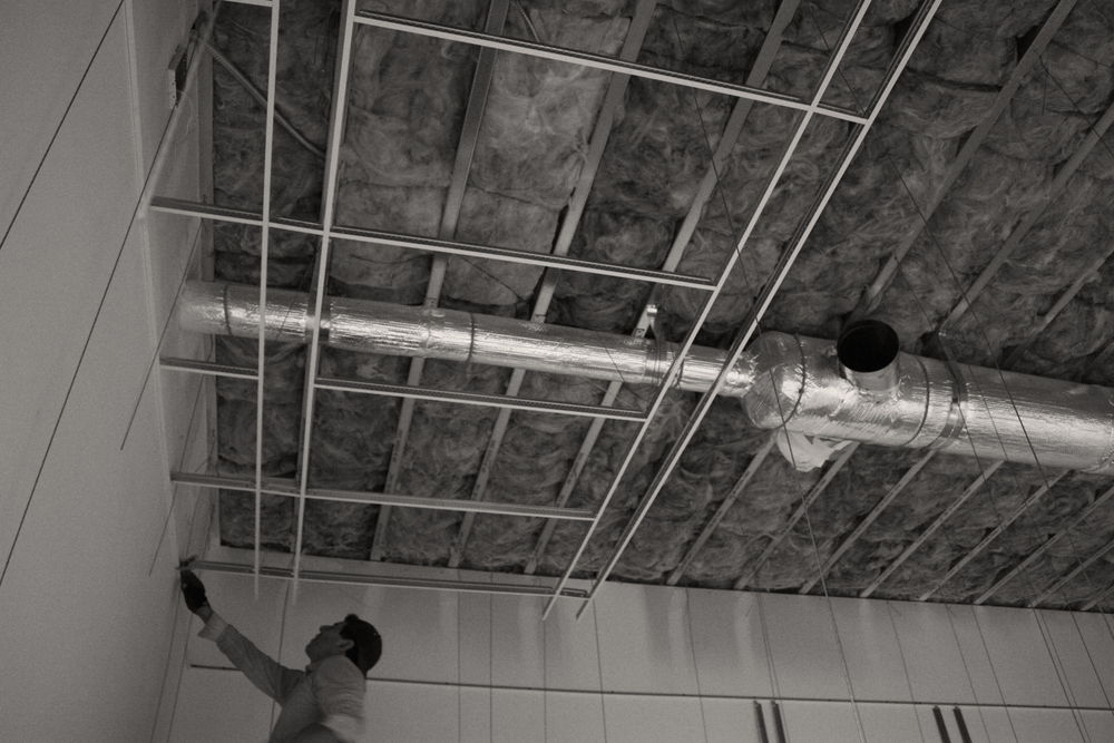 Suspended ceiling being installed in the main conference room.