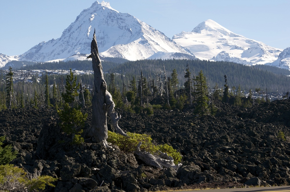 North and Middle Sisters from McKenzie Pass highway (5,325 feet; 1,623 m). The highway here follows the route of an 1860 wagon trail across 65 square miles of lava flow. The area is covered by about 20 feet of snow in winter.
