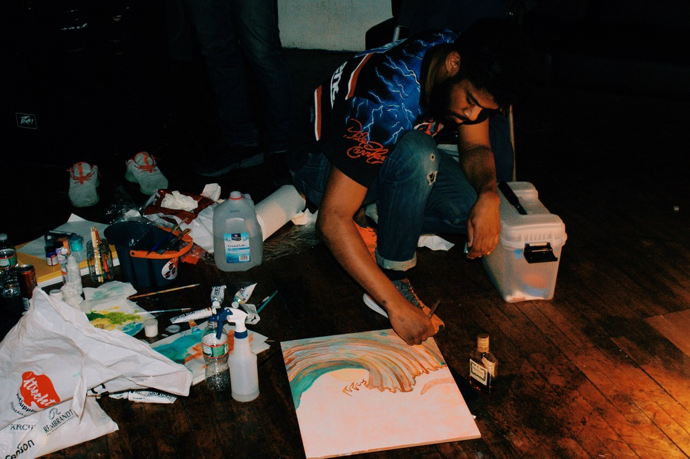 Artist Chantz-Kennedy painting during a live art session to kick off the night. Photo by Brandon McDowell