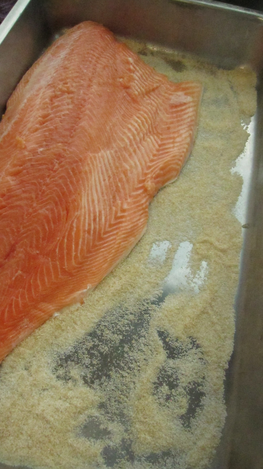 Salmon fillets are placed on top of an even layer of cure