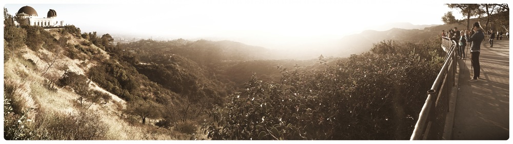 An iphone panoramic shot of the Hollywood Hills from Griffith Observatory (pictured on the left). I believe the Hollywood sign is off in the distance, but completely blown away by the radiant glow of the setting sun.