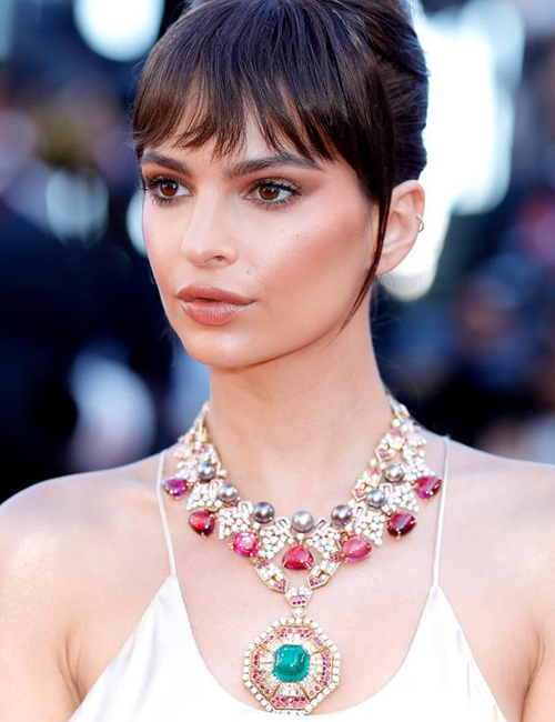 EMILY RATAJKOWSKI  layers two Bulgari necklaces to create a real statement. The long drop pendant set with diamonds, rubies and a stunning emerald is a vintage jewel (made in 1969), the second necklace is from the High Jewellery Collection and is set with pearls, rubellites and diamonds.