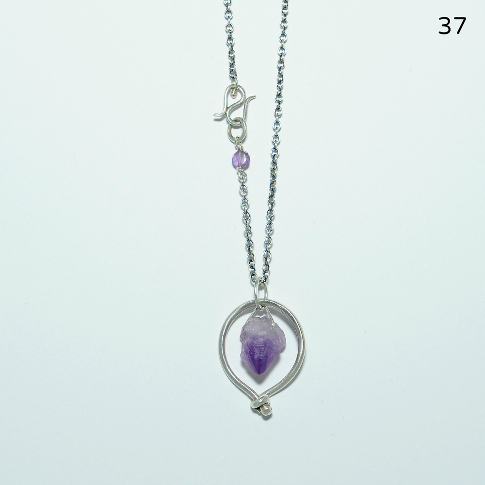 A natural amethyst crystal with gradating shades of purple is suspended inside a sterling, hammered ring with my signature bead-closure wrap. The cable chain is 19 inches in length, and the pendant is one inch in diameter.   $134
