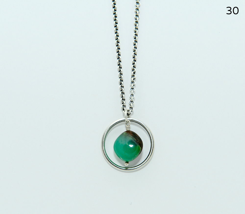 A lustrous, green and brown chrysoprase stone is encircled by a hammered sterling ring. This timeless pendant measures one inch in diameter and is suspended from a 17-inch sterling cable chain.   $146