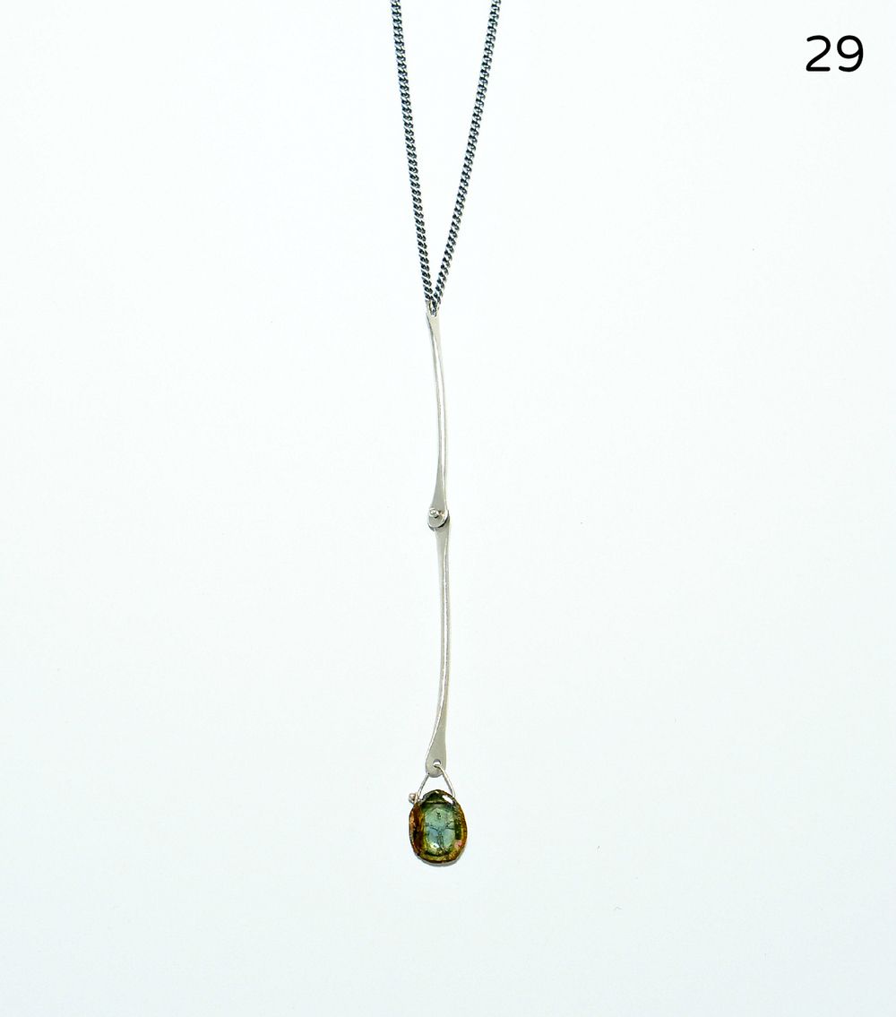 A three-and-a-half inch sterling hinged bar moves freely and holds a translucent blue/green tourmaline slice at its tip. The slim curb chain measures 17 inches in length.   $134