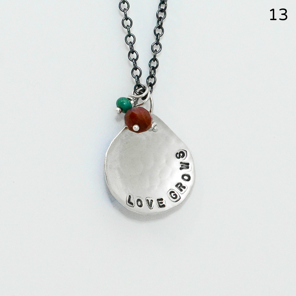 "This sterling ""Love Grows"" necklace, inspired by the lotus leaf, is hand-cut from sterling and hammered so that it's slightly concave. An opaque, deep-pink sapphire and small piece of green turquoise affirm the sentiment of the quote. The charm measures roughly one-inch in diameter, and the oxidized cable chain is 18 inches in length.   $155"