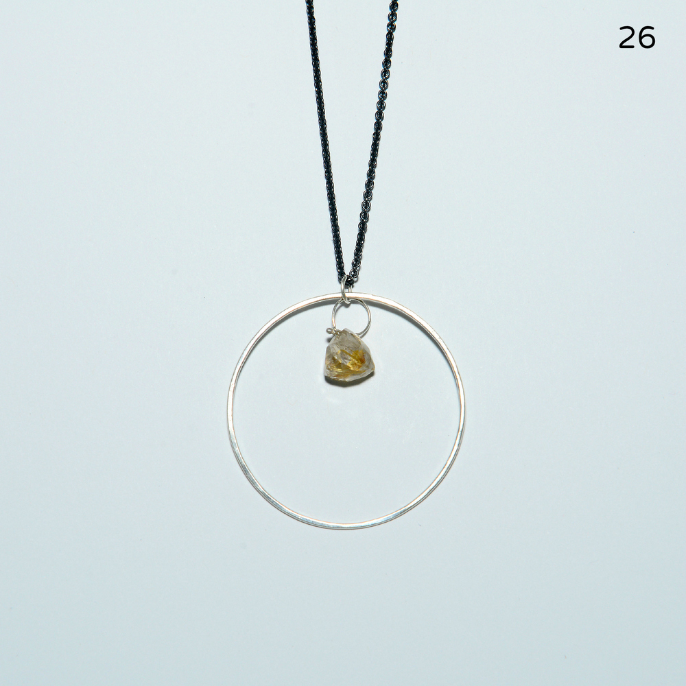 A thin, hammered circle measuring one inch in diameter has a gorgeous, triangular-cut piece of rutilated quartz inside. This pretty pendant hangs from an 18- inch, slim-but-sturdy oxidized chain.   $118