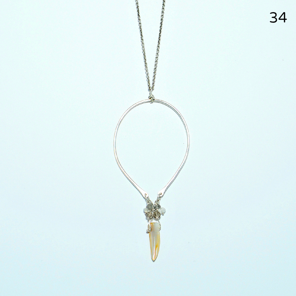 "A lustrous, mother-of-pearl ""tusk"" adorned with tiny rainbow moonstones, labradorites, and smoky quartz is suspended from a  thin, hammered, sterling teardrop.  The cable chain measures 18 inches, and the pendant is three-and-a-half inches in length.   $148"