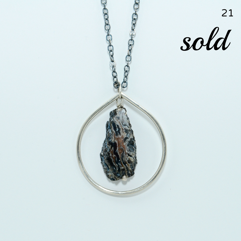 Browns, creams, and gray tones mingle beautifully in this natural agate stone that is framed by a hammered sterling teardrop. Chain is oxidized and measures 22 inches long. Pendant is 2 inches in diameter.   $148
