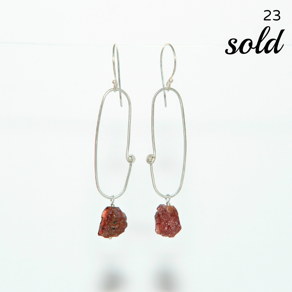 These sterling oblong earrings are lightly hammered and secured with my signature wire wrapped bead. Beautiful, slightly translucent red garnet sways at the bottom of each. Earrings hang 2 inches from the ear lobe.   $68