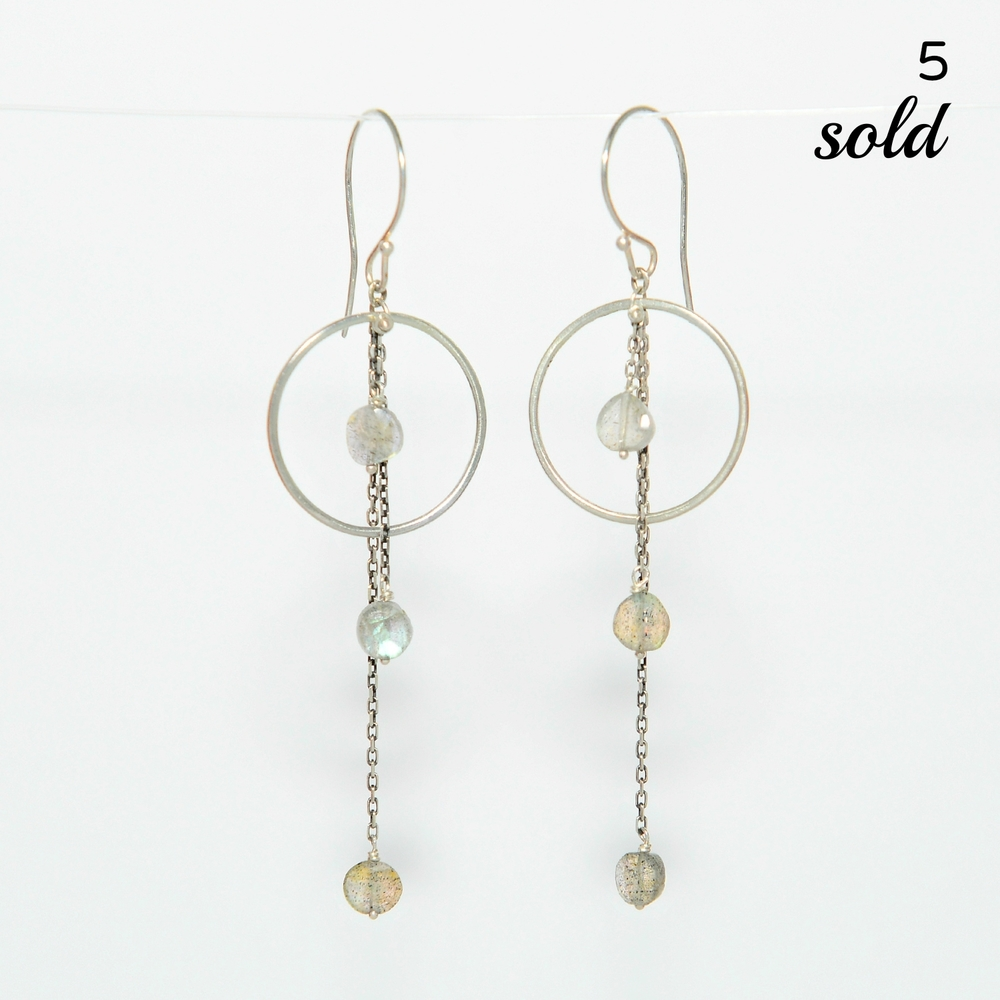 These hammered hoop earrings measure an inch in diameter and have three thin chains bearing gorgeous, iridescent labradorite stones. They hang 2 inches from the ear lobe.   $124