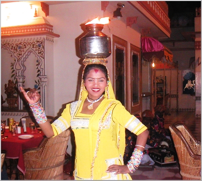This young dancer is balancing a pot with fire on her head and smiling. I am impressived.
