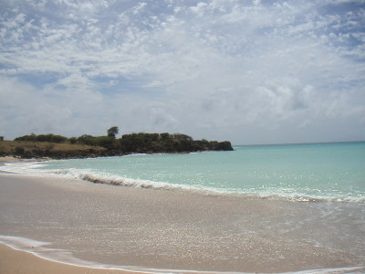 The waves gently breaking on the white sand in one of the small coves in perfect Mint.