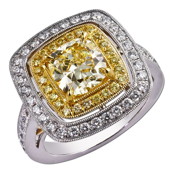 Exceptionally crafted and vintage inspired, bead set round yellow diamonds and round diamonds enhance a magnificent yellow cushion cut center diamond.