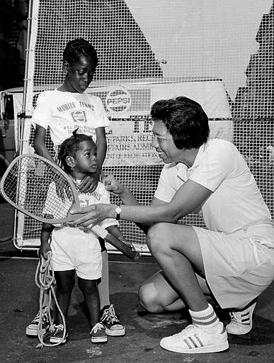 Althea Gibson shows the first tennis racket she used in 1942 on the streets of Harlem to Tiny Huston, 9, and her sister Monica, 1, in New York City, July 11, 1973.    Gibson was born in Silver, South Carolina in 1927 and soon moved with her family to Harlem. She struggled in the classroom but excelled in sports and found her way to the Harlem River Tennis Courts in 1941. Gibson went on to win the Wimbeldon and U.S. Open championships in 1957 and 1958.