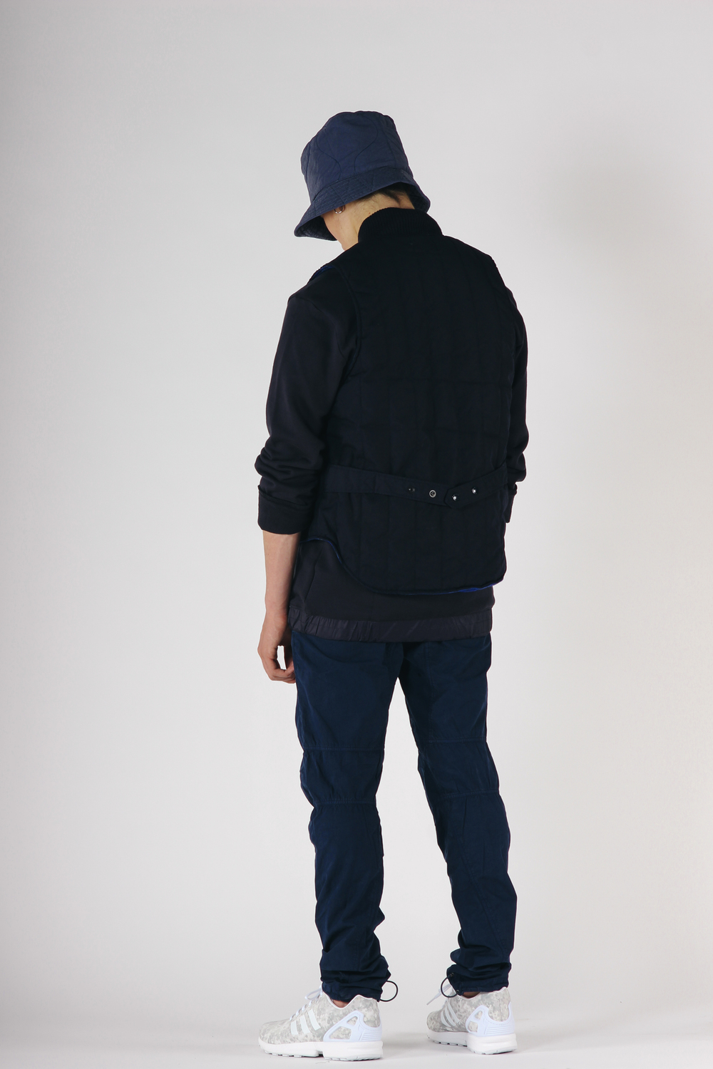 Chapeau: Engineered Garments Quilted Bucket Hat Gilet: Engineered Garments Primaloft Fridge Vest Haut: Still Good Hybrid Crewneck Pants: maharishi Twisted Knee Pant Chaussures: adidas Originals x White Mountaineering ZX Flux