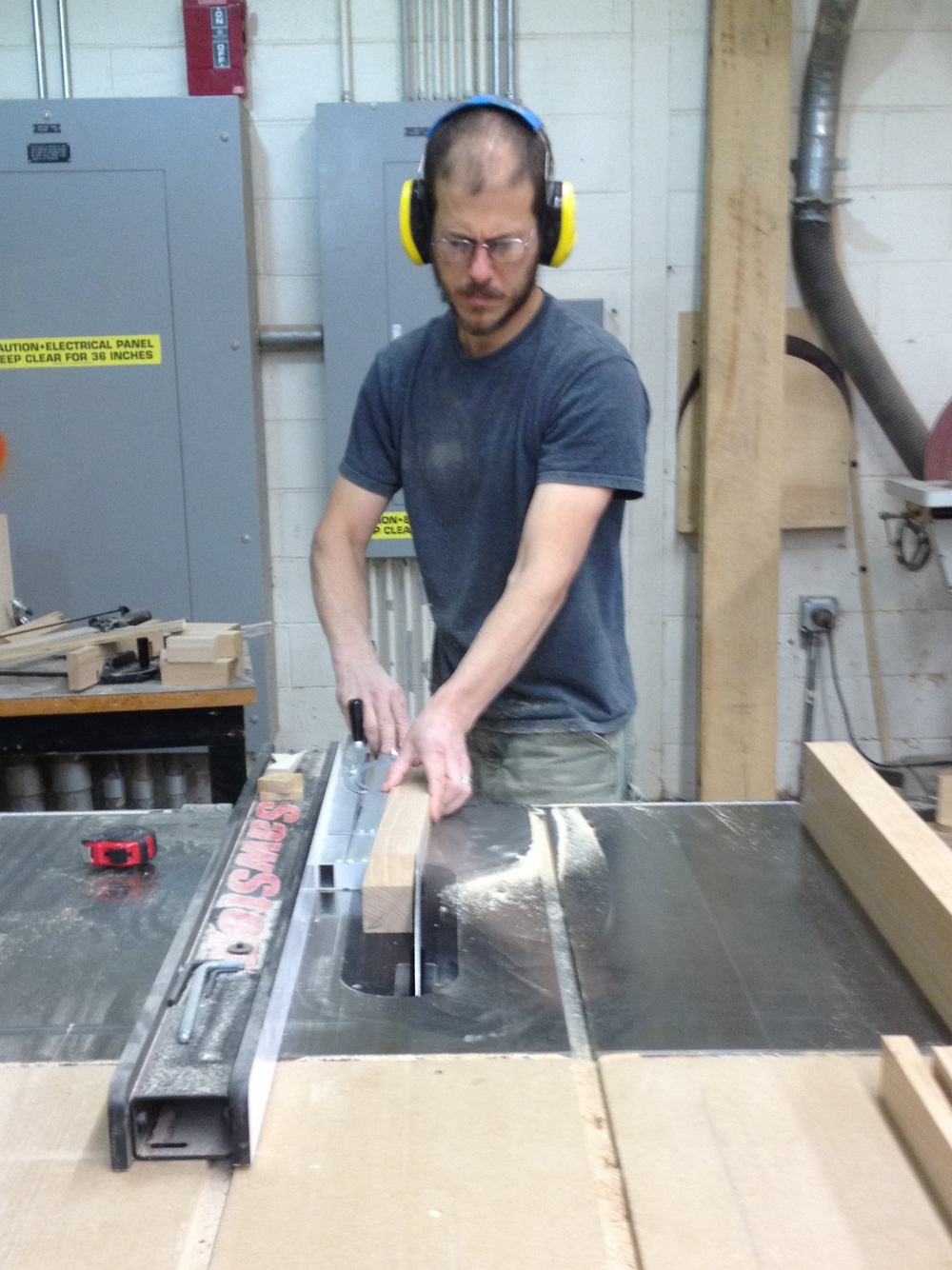 Tapering the legs on the tablesaw with an adjustable jig.