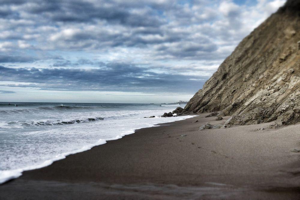 The tiny beach lies between tumbling stone cliffs...