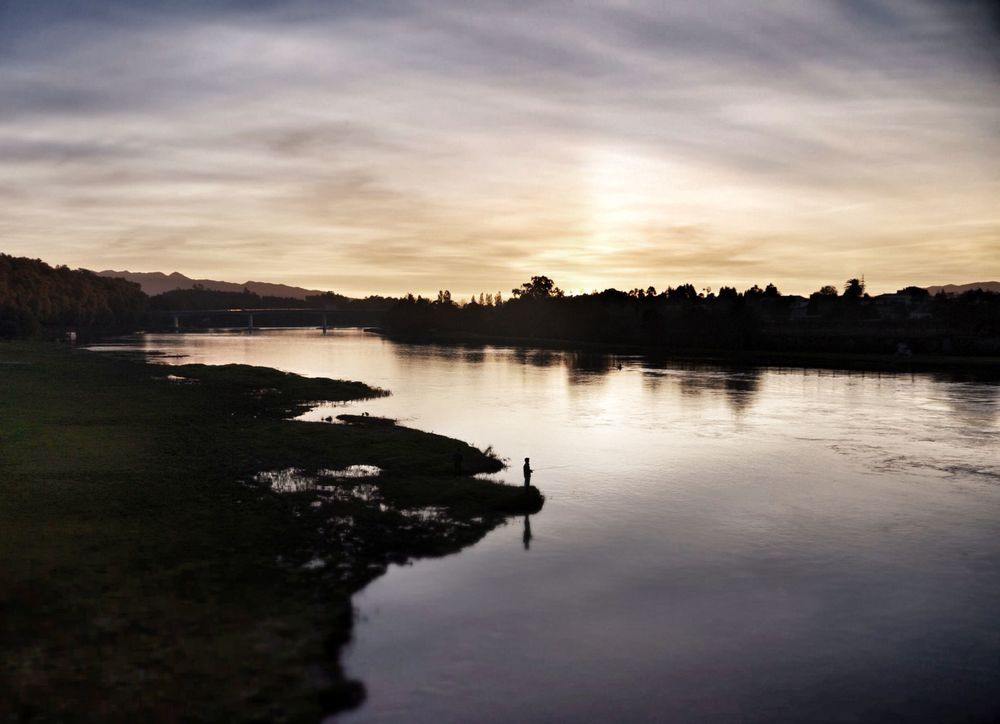 A lone fisherman stays on as the sun sets over the river Lima