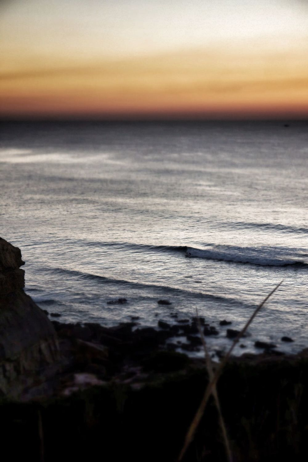 A lone surfer catches a wave as the sun sets in Peniche