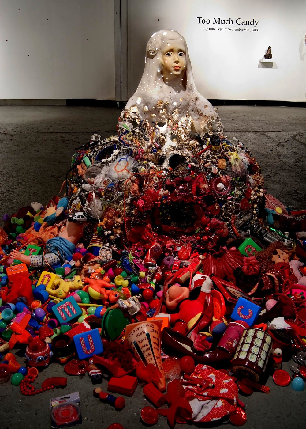 The Princess , 2004. Installed at Living Arts, Tulsa, Oklahoma as part of  Too Much Candy.  Found objects, ceramic (the head),  light bulb and fixture (the head lights up from within), fabric,  plants (they lived inside the skirt, they were visible through a hole in the front),wire, thread, gouache. Variable dimensions, about four feet tall.