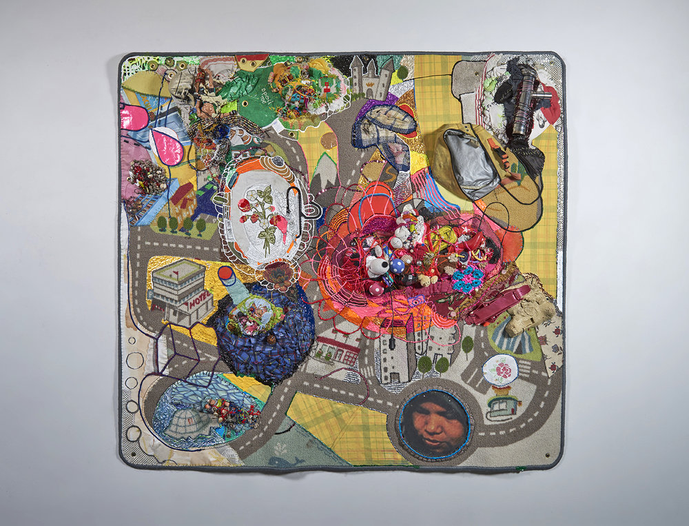 """Crawling on Cancer (The Teflon Toxin by Sharon Lerner  ), 2016. 52"""" x 55"""" x 6"""", carpet, trim, photo, thread, found objects, fabric paint, fabric, grommets"""