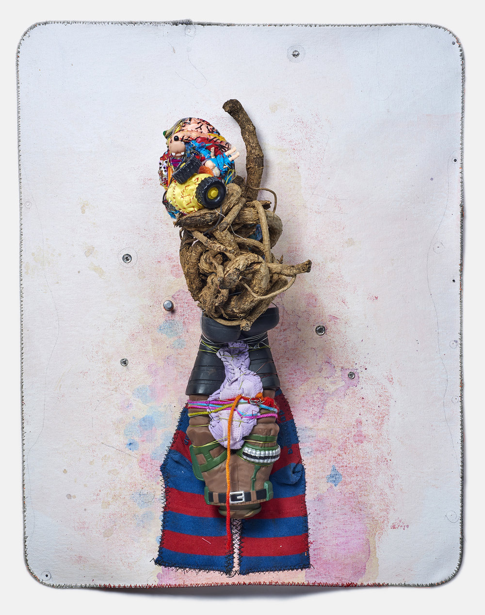 "Nature, Fashion & War    2016,   22 ½"" 17 ½"" x 8"",  metal cable, pencil, gouache, acrylic, yarn, fabric, thread, & found objects (including: a plant root, socks, soldier doll legs) on canvas"