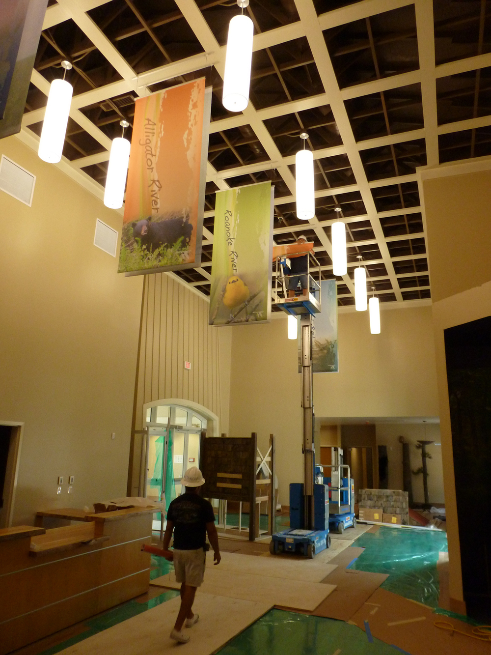 Pendant lights and banners are used to enhance high lobby ceilings and add to exhibit spaces.