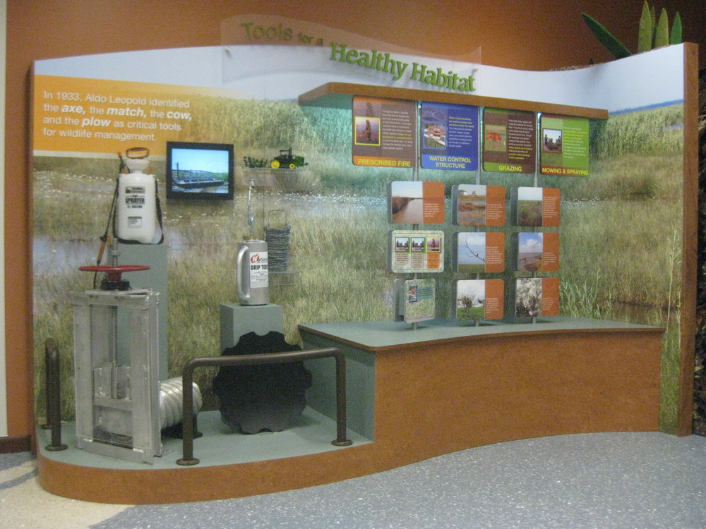 Man's effects on nature are discussed in this interactive spinning-panel display. Tools of the trade are securely displayed and feature an interactive water control structure. Looping video adds another dimension to the exhibit.