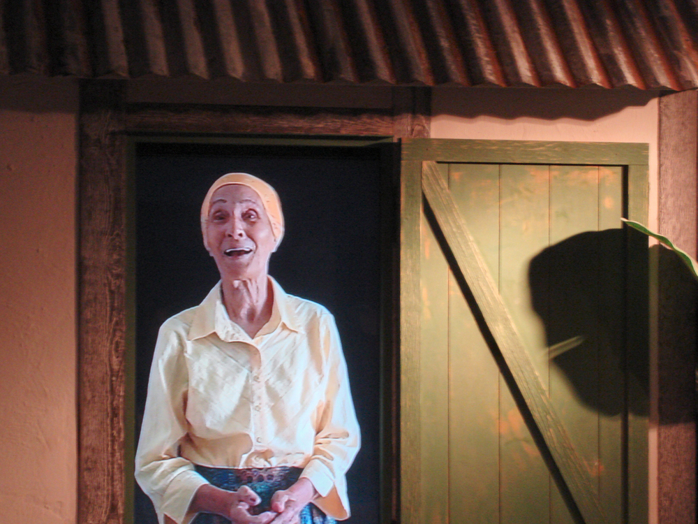 A virtual Miss Hattie welcomes visitors from a re-created historic Cayman cottage.