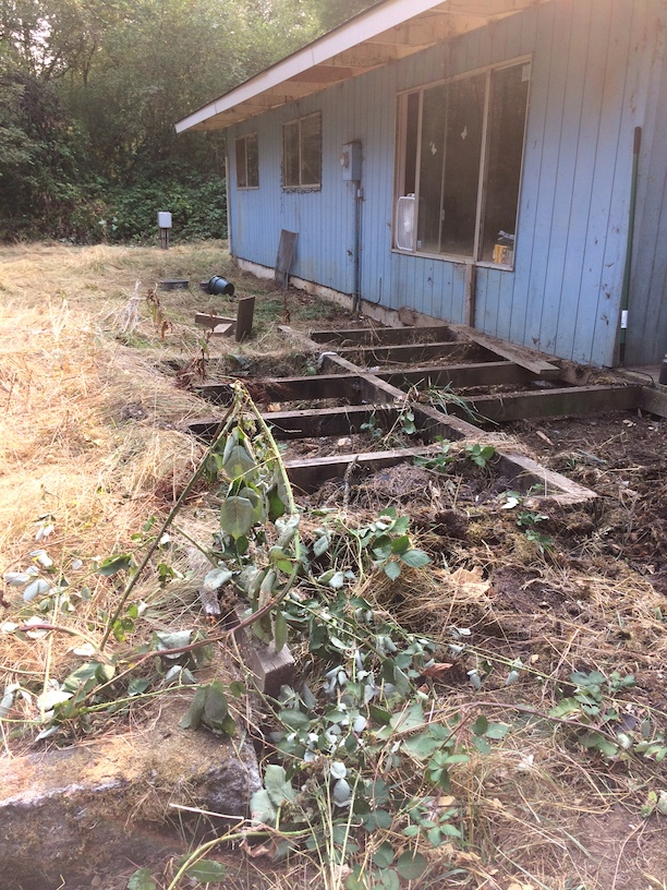 Some day this deck will be repaired and the house will be painted green and there will be a small border of stones around the outside.