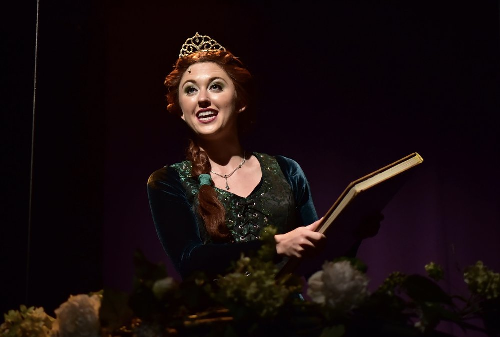 "The Herald Bulletin - ""You won't find a one-dimensional damsel in distress in Emily Grace Tucker's role as Princess Fiona. She's a fiery female who values tradition, but has her own complexities that lead her down another path. She holds her own alongside the boys, and her singing stands out"". CLICK HERE FOR FULL REVIEW."