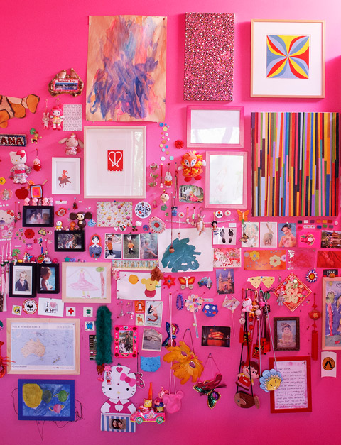Lana and Scarlet have created a collage of framed artworks and collectables on the magenta magnetic walls in their bedroom.
