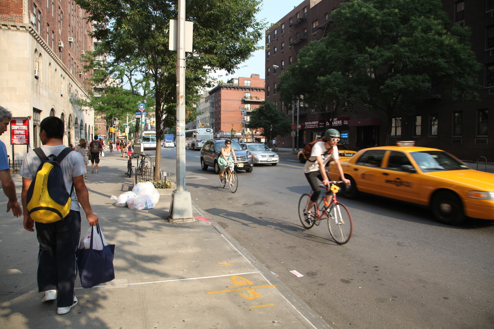 A Brooklyn Street with cyclists pedaling through traffic.