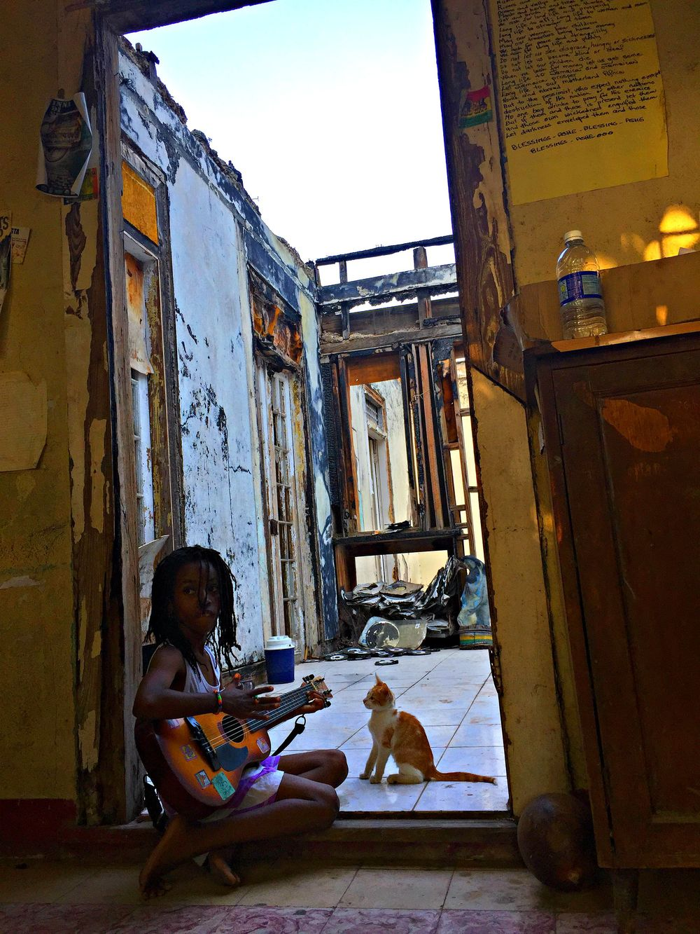 "Former studio and home for brilliant Jamaican band Uprising Roots. Sadly, archives of music and recording equipment got burned down in a fire.  Here ""Cookie"", daughter of one of the musicians, plays a song for her cat."